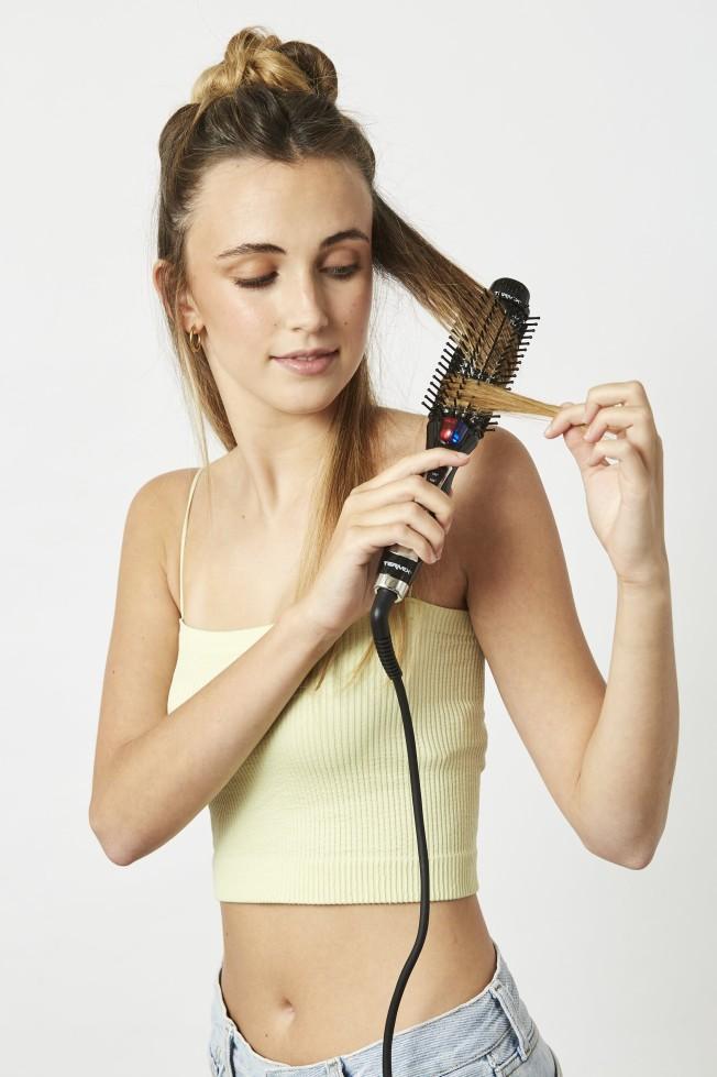 Chica usando el cepillo eléctrico de Termix