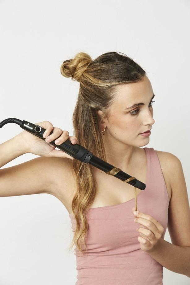Chica rizándose el pelo