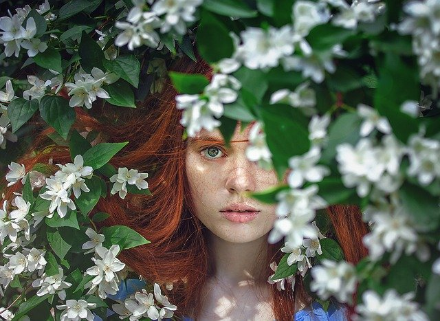 Chica con flores al fondo